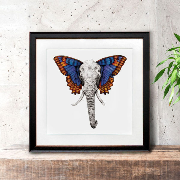 Print of an elephant with colourful butterfly wings in a black frame on a wooden bench against a wall