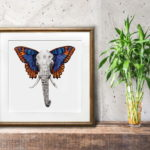 Print of an elephant with colourful butterfly wings in a gold frame on a wooden shelf leaning against a wall