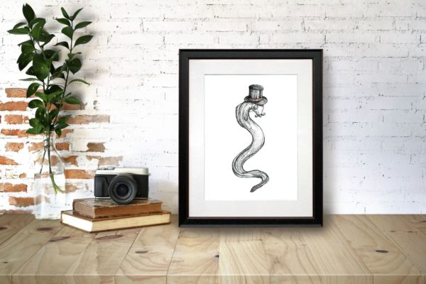 """Black and white print of an eel wearing a top hat with the text """"Genteel"""" in a black frame on a wooden desk"""