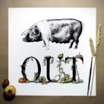 Print of a saddleback pig above bold black lettering decorated with vegetables growing around and beside the letters