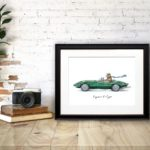Print of a Jaguar wearing a flat cap and scarf driving a green jaguar e-type in a black frame sitting on a wooden desk