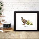 Print of a partridge and pears portraying 'A Partridge in a Pear Tree' in a black frame on a desk against a brick wall