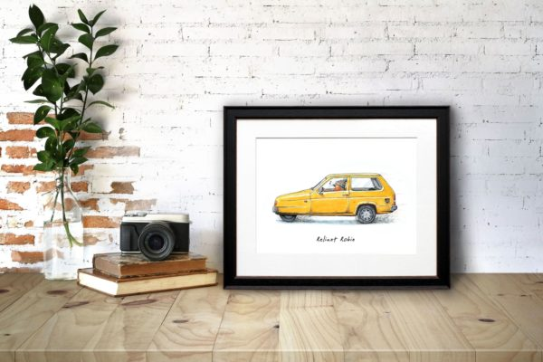 Print of a robin wearing a woolly hat driving a yellow reliant robin car in a black frame on a desk against a brick wall