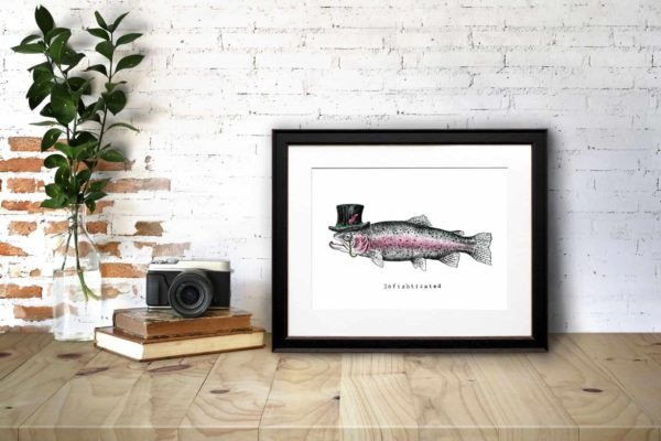 Print of a fish wearing a top hat with a monocle in a black frame on a wooden desk leaning against a white brick wall