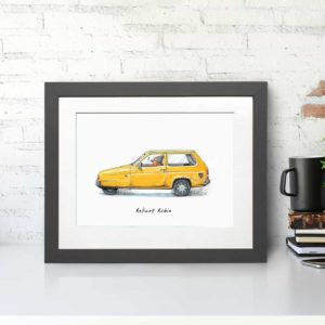 Print of a robin wearing a woolly hat driving a yellow reliant robin car in a grey frame on a white desk against a brick wall