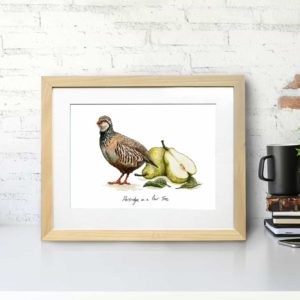 Print of a partridge and pears portraying 'A Partridge in a Pear Tree' in a light wood frame on a white desk against a wall