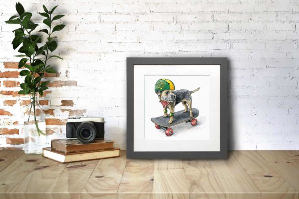 Print of a border terrier skateboarding with a green and yellow helmet and knee pads in a grey frame on a wooden shelf