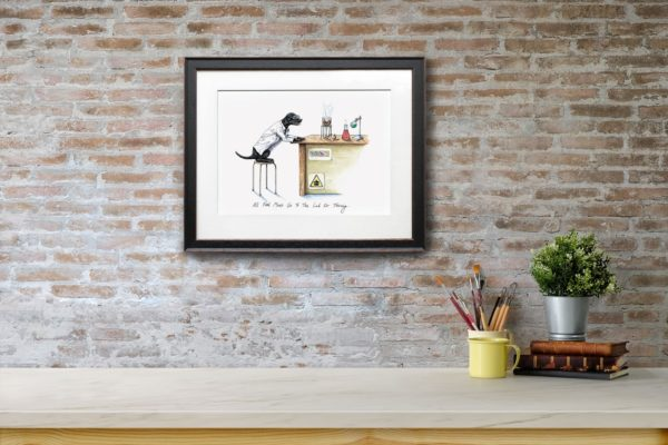 Print of a black labrador wearing a white Lab coat sitting at a desk in a science lab in a black frame on a red brick wall