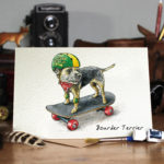Greetings card of a border terrie skateboarding wearing a green and yellow helmet and knee pads on a wooden table