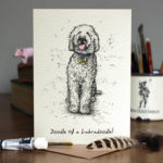Greetings card of a black and white drawing of a labradoodle on a wooden table