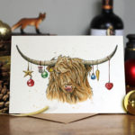 Christmas card of a Highland cow with colourful Christmas baubles hanging from its horns on a wooden table