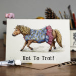 Greetings card of a Shetland pony trotting in a blue dress with a horseshoe pattern and pink frills on a wooden table