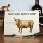 Greetings card of a brown cow saying alright thanks with How Now Brown Cow text on a wooden table