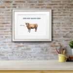 Print of a brown cow in a white frame on a red brick wall above a white shelf with a plant, books and pens