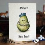 Father's Day card of a green pear with a string of garlic round its neck wearing a blue beret on a wooden table