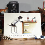 Greetings card of a black Labrador wearing a white Lab coat sitting at a desk in a science lab on a wooden table