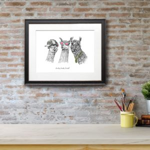 Print of three black and white llamas wearing sunglasses, a cap and a gold chain in a black frame on a red brick wall