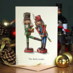 Christmas card of a green nutcracker toy soldier kicking a red toy soldier on a wooden table with Christmas decorations