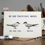 Greetings card of a black and white tern wearing a brown flat cap standing directly opposite another tern on a wooden table