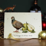 Christmas card of a partridge and pears portraying A Partridge and a Pear Tree sitting on a wooden table with Christmas decorations