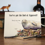 Congratulations Greetings card of a seal and a crab celebrating success while lying on colourful rocks on a wooden table