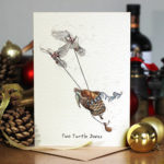 Christmas card of two doves with a turtle in a basket portraying Two Turtle Doves on a table with Christmas decorations