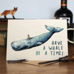 A greetings card of a whale wearing a party hat on a wooden table