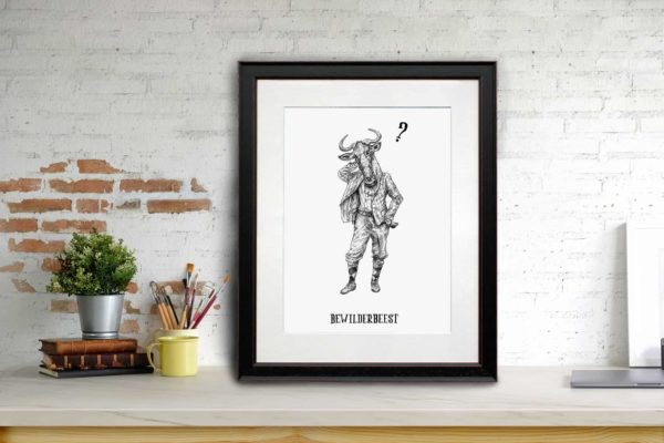 Print of a wildebeest dressed in human clothing in a black frame sitting on a shelf learning against a white brick wall