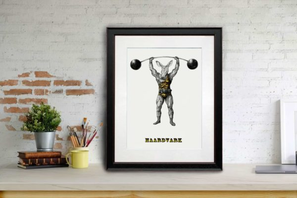 Print of an aardvark dressed as strong man wearing a leotard and lifting a barbell in a black frame sitting on a shelf