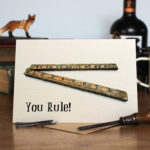 Greetings card of a vintage wooden ruler sitting on a wooden table