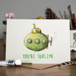 Greetings card of a lime disguised as a submarine with windows and a propeller sitting on a wooden table