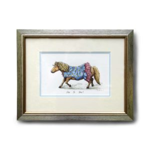Original artwork in a silver frame of a Shetland pony trotting along in a blue dress with a horseshoe pattern and pink frills