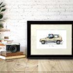 An original illustration of an old yellow fiat panda car being driven by a panda wearing a sunhat in a black frame on a desk