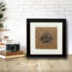 Original pen and acrylic drawing of a sheep on brown paper in a black frame sitting on a wooden shelf against a white brick wall